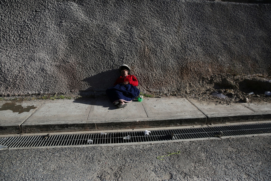 A woman lays on the sidewalk after attending a wedding party in the town of Nueva Fuerabamba in Apurimac, Peru, October 2, 2017. Reuters Photo/Mariana Bazo