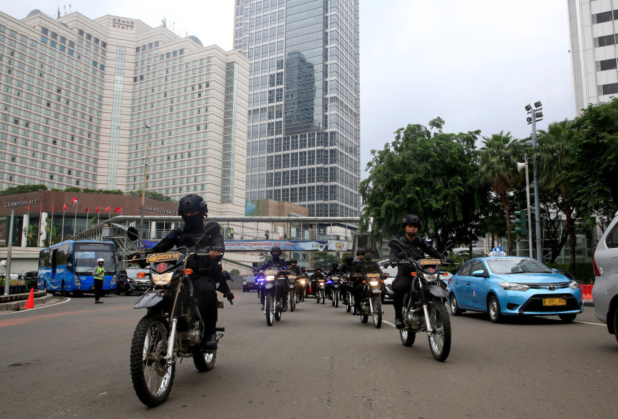 Mobile brigade policemen on motorbikes ride through the business district ahead of Christmas and New Year's celebrations in Jakarta on Dec. 21, 2017. (Reuters Photo/Beawiharta)