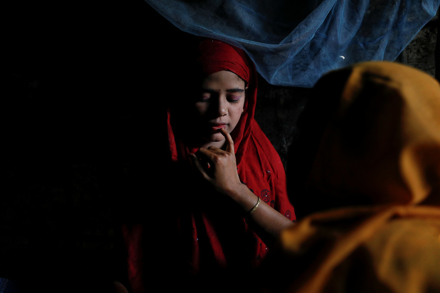 Shofika Begum, 18, is helped with make-up by her brother's wife on the day she marries Saddam Hussein, 23, both Rohingya refugees, at Kutupalong refugee camp near Cox's Bazar, Bangladesh, December 11, 2017. The newly wed couple, both from the village of Foyra Bazar in Maungdaw township that was burnt by the Myanmar military, fled with their families and other Rohingya some three months ago, Saddam Hussein said. They knew each other from before escaping from Myanmar and were planning to get married but managed to do so only now, as refugees living in overcrowded Kutupalong refugee camp. Reuters Photo/Damir Sagolj