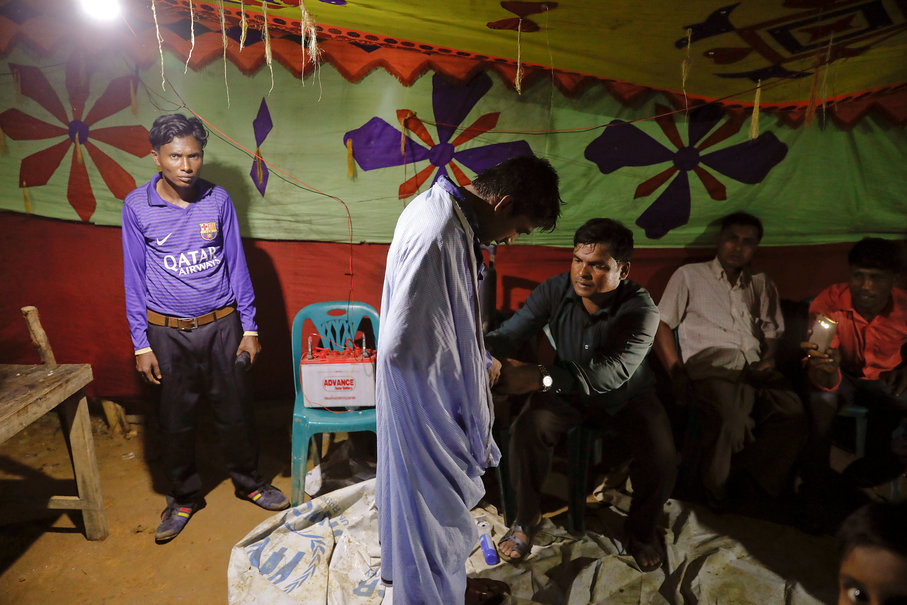 Saddam Hussein, 23, gets dressed before marrying Shofika Begum, 18, both Rohingya refugees, at the Kutupalong camp near Cox's Bazar, Bangladesh, December 11, 2017. The newly wed couple, both from the village of Foyra Bazar in Maungdaw township that was burnt by the Myanmar military, fled with their families and other Rohingya some three months ago, Saddam Hussein said. They knew each other from before escaping from Myanmar and were planning to get married but managed to do so only now, as refugees living in the overcrowded Kutupalong refugee camp. Reuters Photo/Damir Sagolj