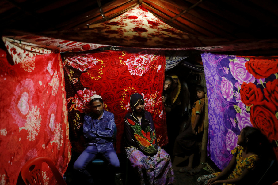 Rohingya refugees Saddam Hussein, 23, and Shofika Begum, 18, pose for a picture in a tent decorated with blankets just after getting married at the Kutupalong refugee camp near Cox's Bazar, Bangladesh, December 11, 2017. The newly wed couple, both from the village of Foyra Bazar in Maungdaw township that was burnt by the Myanmar military, fled with their families and other Rohingya some three months ago, Saddam Hussein said. They knew each other from before escaping from Myanmar and were planning to get married but managed to do so only now, as refugees living in the overcrowded Kutupalong refugee camp.  Reuters Photo/Damir Sagolj