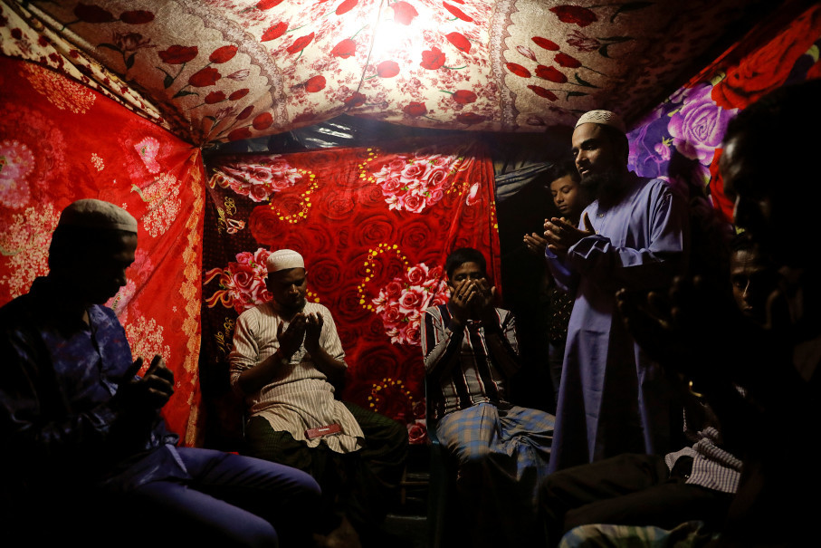 An muslim cleric (R) performs a wedding ritual for Rohingya refugees Saddam Hussein (L), 23, and Shofika Begum, 18, who stays in a separate room, at the Kutupalong camp near Cox's Bazar, Bangladesh, December 11, 2017. The newly wed couple, both from the village of Foyra Bazar in Maungdaw township that was burnt by the Myanmar military, fled with their families and other Rohingya some three months ago, Saddam Hussein said. They knew each other from before escaping from Myanmar and were planning to get married but managed to do so only now, as refugees living in the overcrowded Kutupalong refugee camp. Reuters Photo/Damir Sagolj