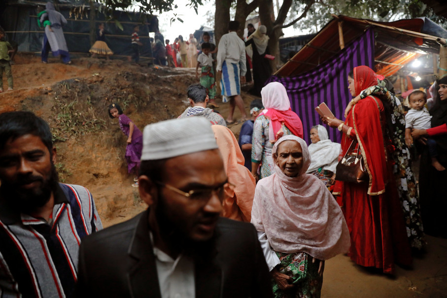 People attend a wedding party for Rohingya refugees Saddam Hussein, 23, and Shofika Begum, 18, at the Kutupalong camp near Cox's Bazar, Bangladesh, December 11, 2017. The newly wed couple, both from the village of Foyra Bazar in Maungdaw township that was burnt by the Myanmar military, fled with their families and other Rohingya some three months ago, Saddam Hussein said. They knew each other from before escaping from Myanmar and were planning to get married but managed to do so only now, as refugees living in overcrowded the Kutupalong refugee camp. Reuters Photo/Damir Sagolj