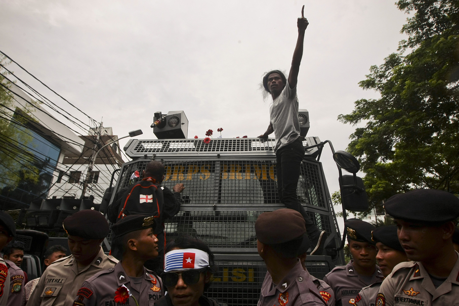 A demonstrator climbs on top of a police vehicle in Jakarta on Friday (01/12). (JG Photo / Yudha Baskoro)