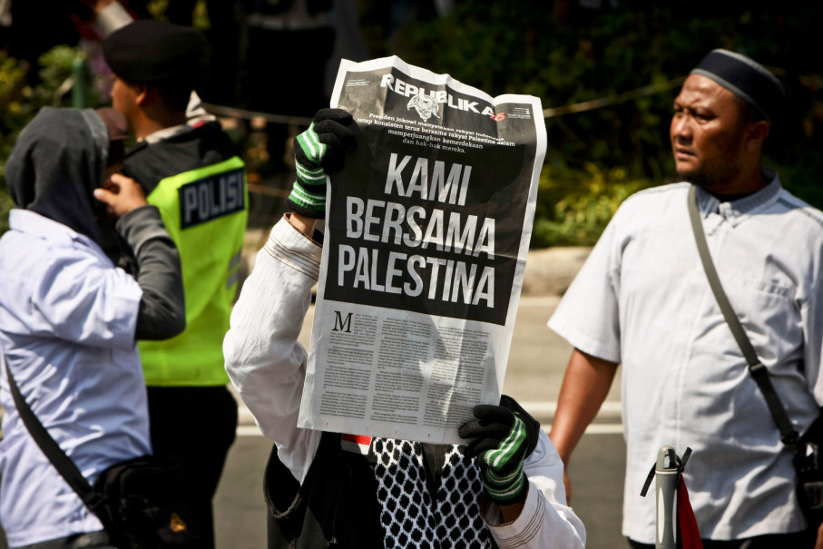 """A demonstrator holds up a newspaper with the headline """"We're with the Palestinians."""" (JG Photo/Yudha Baskoro)"""
