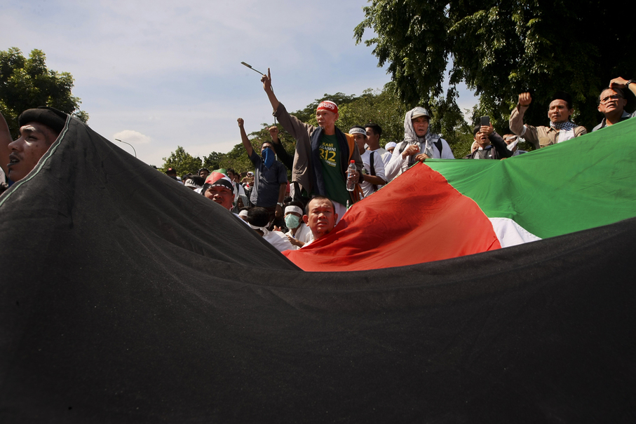 Protesters wave a Palestinian flag in front of the US Embassy. (JG Photo/Yudha Baskoro)