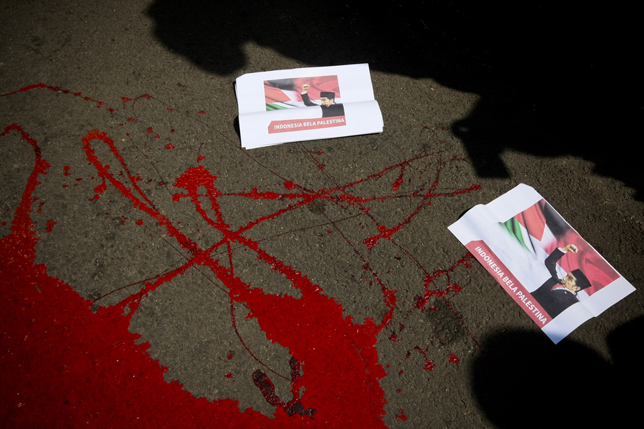 "Posters of President Joko Widodo with the caption ""Indonesia Defends Palestine"" are scattered on the street painted with fake blood. (JG Photo/Yudha Baskoro)"