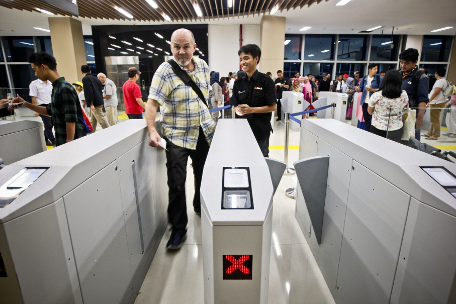 An airport train passenger passes through the turnstile at Sudirman Baru Station on Wednesday (27/12). (JG Photo/Yudha Baskoro)