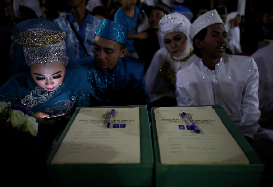 A bride looks at her mobile phone during the mass wedding. (Reuters Photo/Darren Whiteside)