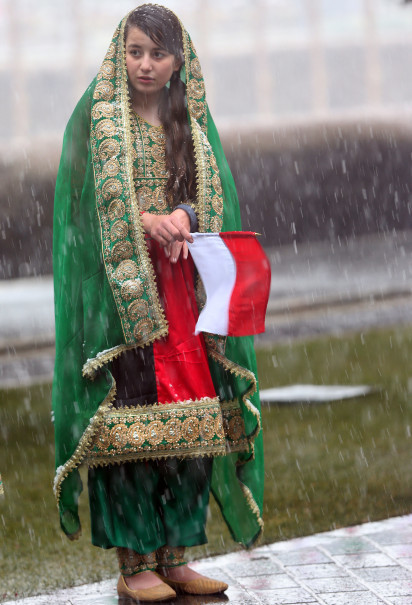 An Afghan girl holds an Indonesian flag in front of the palace. (Reuters Photo/Massoud Hossaini)