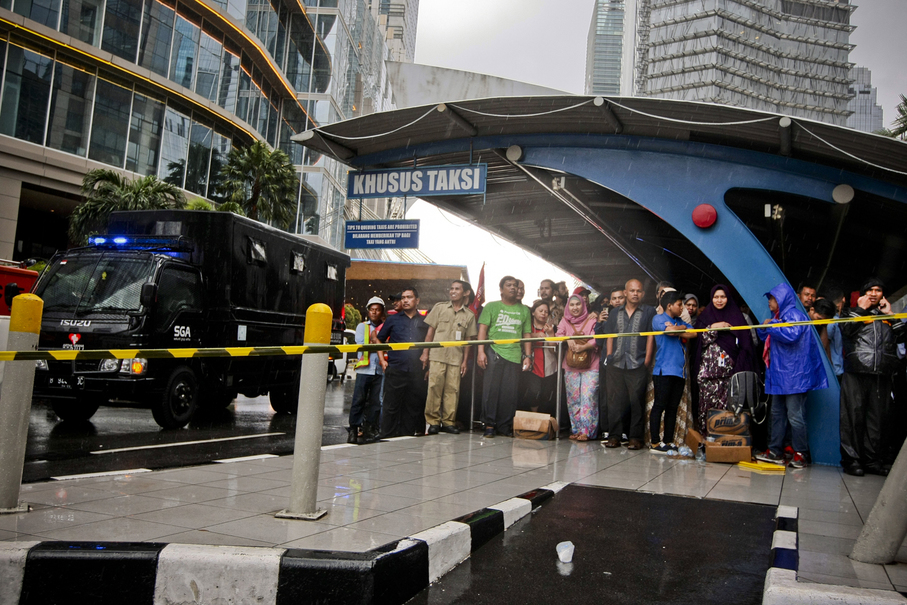 Office staff take shelter from heavy rain while rescue workers evacuate injured victims from the lobby of the Indonesia Stock Exchange (IDX) building in South Jakarta on Monday. (JG Photo/Yudha Baskoro)