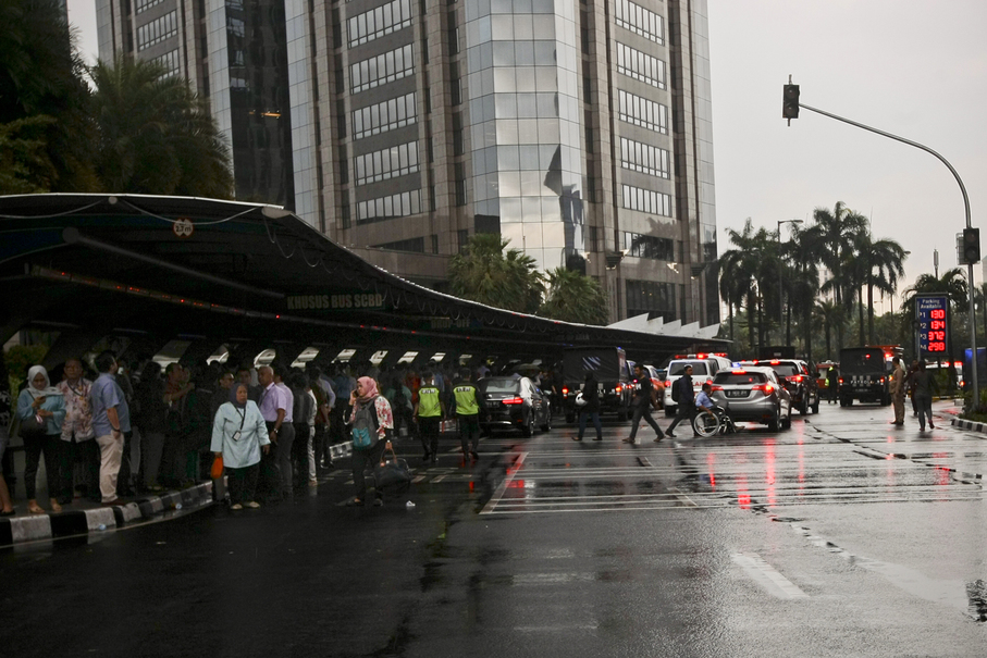 The heavy rain did not hamper the evacuation process but office staff were forced to take shelter at various places outside the affected building. (JG Photo/Yudha Baskoro)