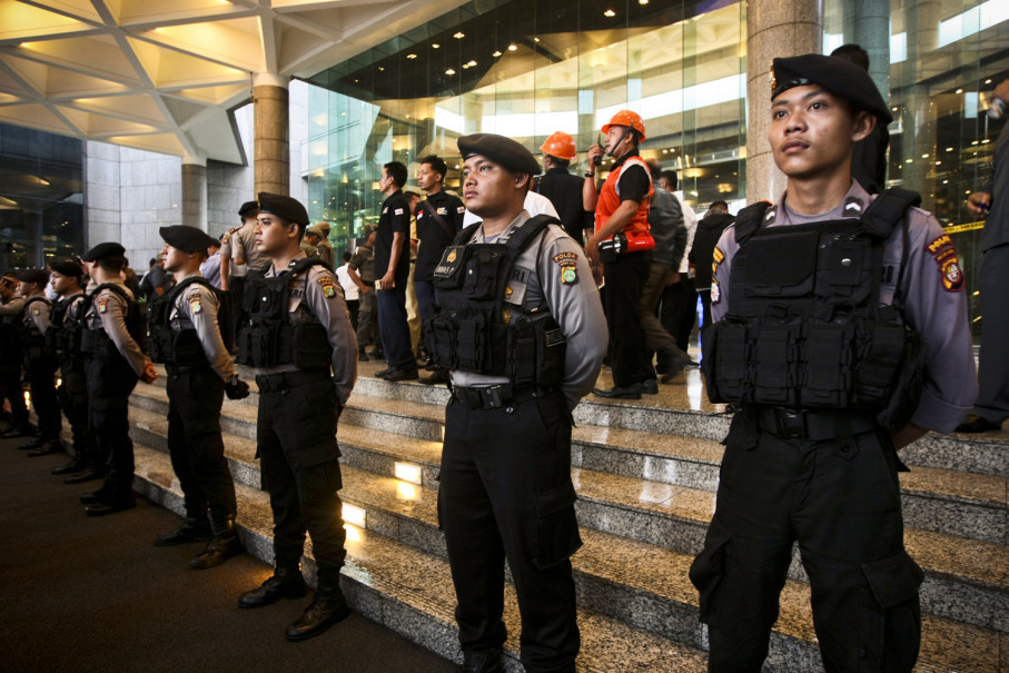 Police officers guard the entrance to Tower 2 while the evacuation continues. Office workers were still allowed to enter through Tower 1. (JG Photo/Yudha Baskoro)