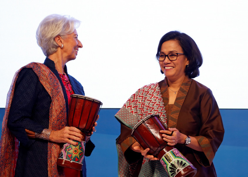 Finance Minister Sri Mulyani Indrawati holds a music percussion beside International Monetary Fund managing director Christine Lagarde during the opening of the IMF conference in Jakarta. (Reuters Photo/Beawiharta)