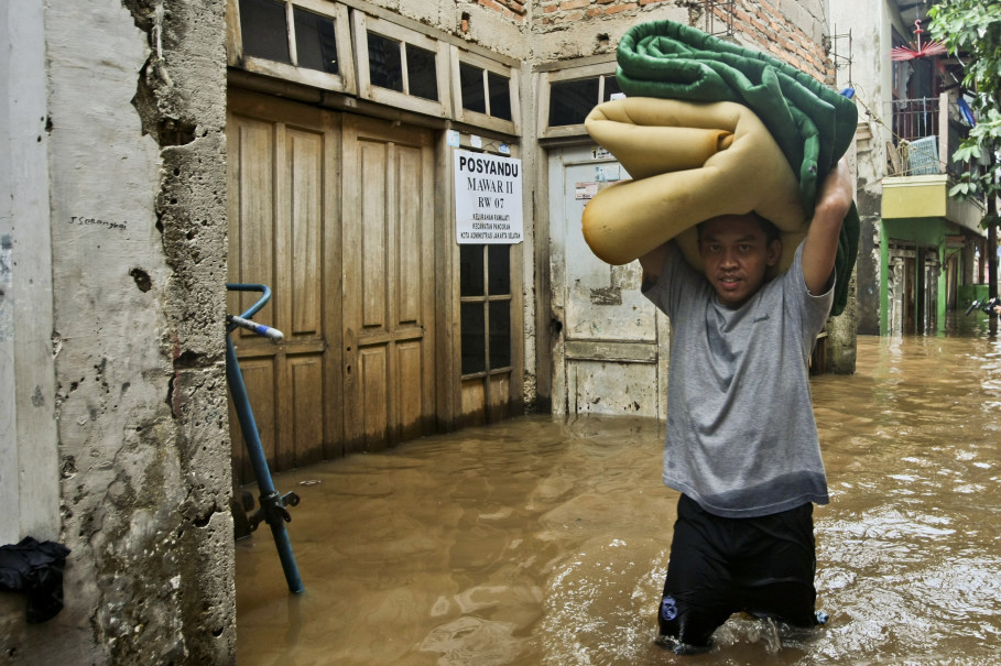 A man tries to save his property, as water entered his home in Rawajati. (JG Photo/Yudha Baskoro)