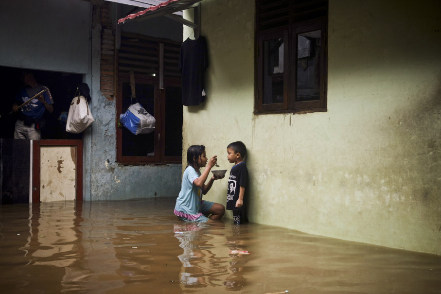 A girl feeds her brother at their flooded house in Rawajati. (JG Photo/Yudha Baskoro)