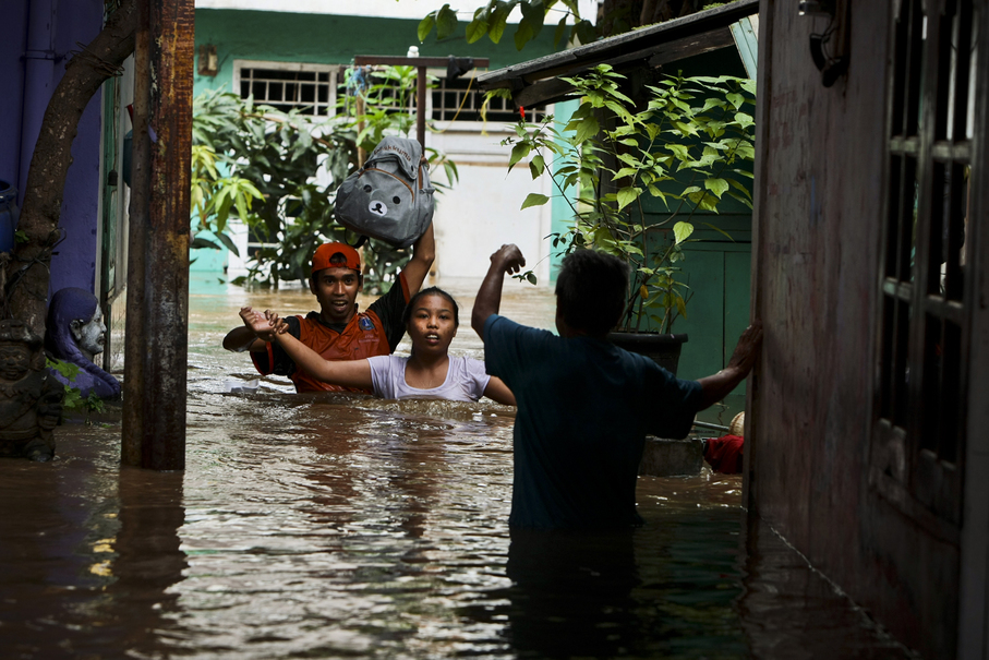 Rescuers help residents evacuate their flooded homes. (JG Photo/Yudha Baskoro)