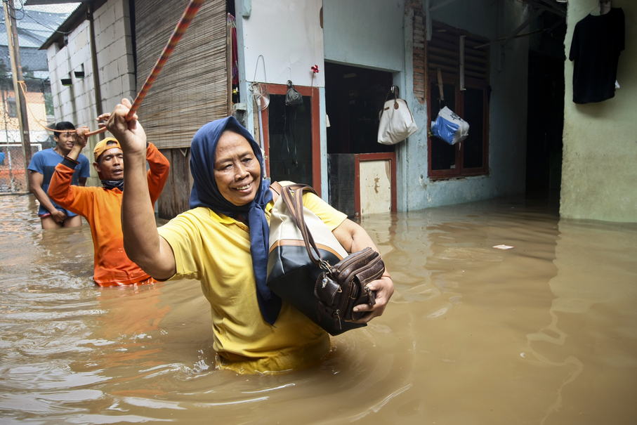 People hold a rope as they are moved to safety from their inundated neighborhood. (JG Photo/Yudha Baskoro)