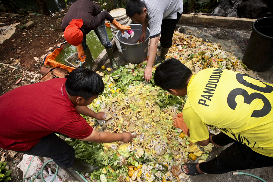 Biomagg chief executive Aminudi, left, and his colleagues sort through organic waste at the company's facilities in Depok on Jan. 25. (JG Photo/Yudha Baskoro)