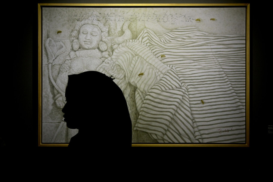 A visitor stands in front of the painting 'Siul Angin di Rekah Batu' (The Wind Whistling in Stone Crevices) by Dyan Anggraini and Landung Simatupang. (JG Photo/Yudha Baskoro)