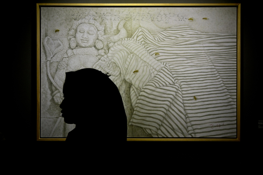 Visitor stands in front of the painting 'Siul Angin di Rekah Bat' (The Wind Whistling in Stone Crevises) at the Perempuan Di Borobudur exhibition at the National Gallery of Indonesia. (JG Photo/Yudha Baskoro)