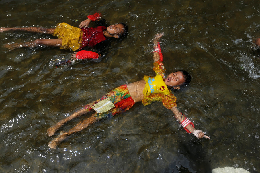 Youth play as sea water rises during high tide at Kali Adem Port in Jakarta, Jan. 3. (Reuters Photo/Beawiharta)