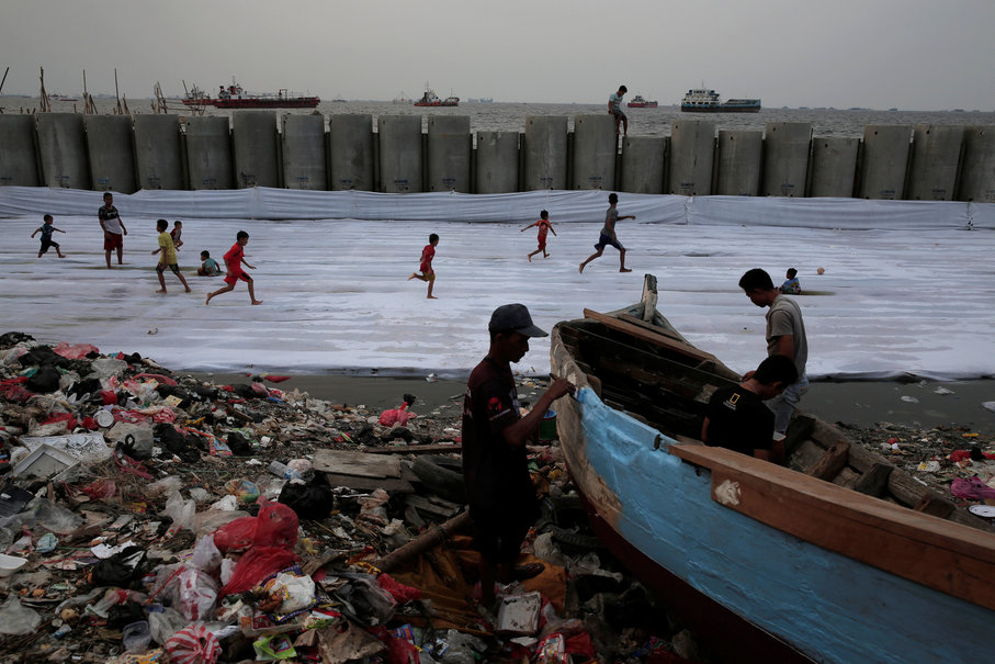 Fishermen repair their wooden boat, while children play football near a new construction of a concrete sea wall in Cilincing, Jakarta, Aug. 22. (Reuters Photo/Beawiharta)
