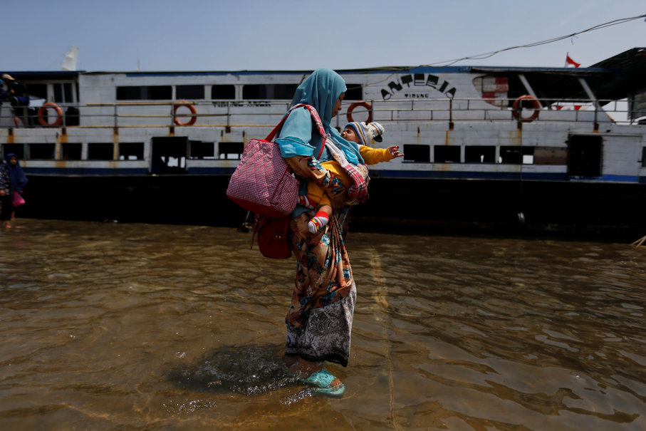A boat passenger holds her baby as she walks through rising sea water during high tide at Kali Adem Port, Jan. 3. (Reuters Photo/Beawiharta)
