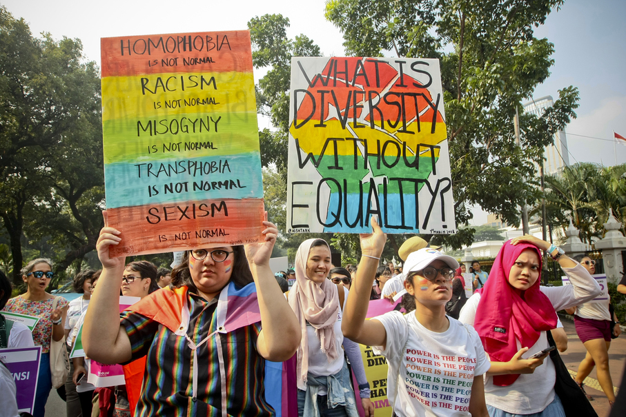 Participants hold up posters during the march. (JG Photo/Yudha Baskoro)