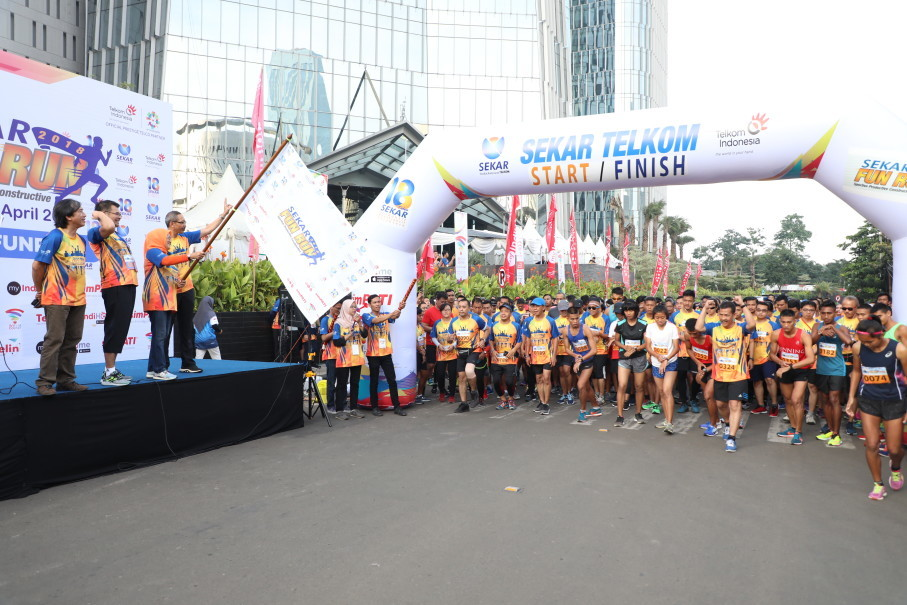 Director General of Industrial Relations Development and Social Security Manpower Ministry of Manpower Haiyani Rumondang, Wholesale & International Services Director of Telkom Abdus Somad Arief and Chairman of SEKAR Telkom waving the flag during the start of SEKAR Telkom Fun Run 2018 in Jakarta, Sunday (8/4) ).