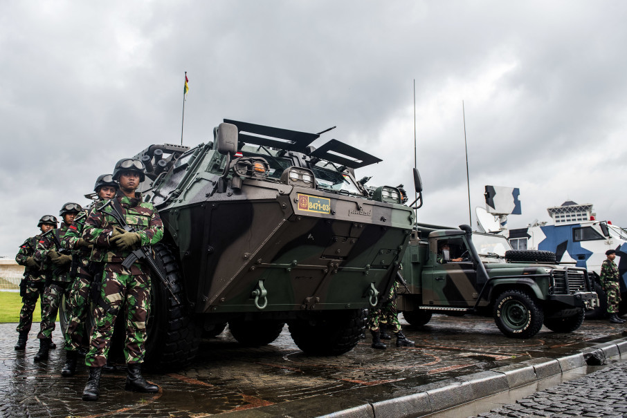 Indonesian soldiers flank an Anoa armored personnel carrier developed by state-owned arms manufacturer Pindad. (Antara Photo/M Agung Rajasa)