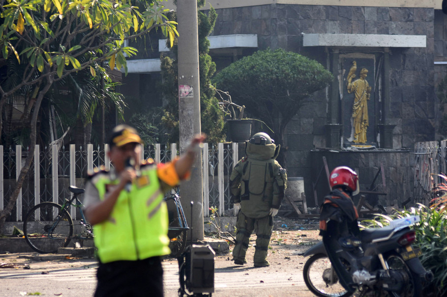 A member of the police bomb squad unit examines the site of an explosion outside the Immaculate Santa Maria Catholic Church in Surabaya, East Java. (Antara Photo/M Risyal Hidayat/via Reuters)