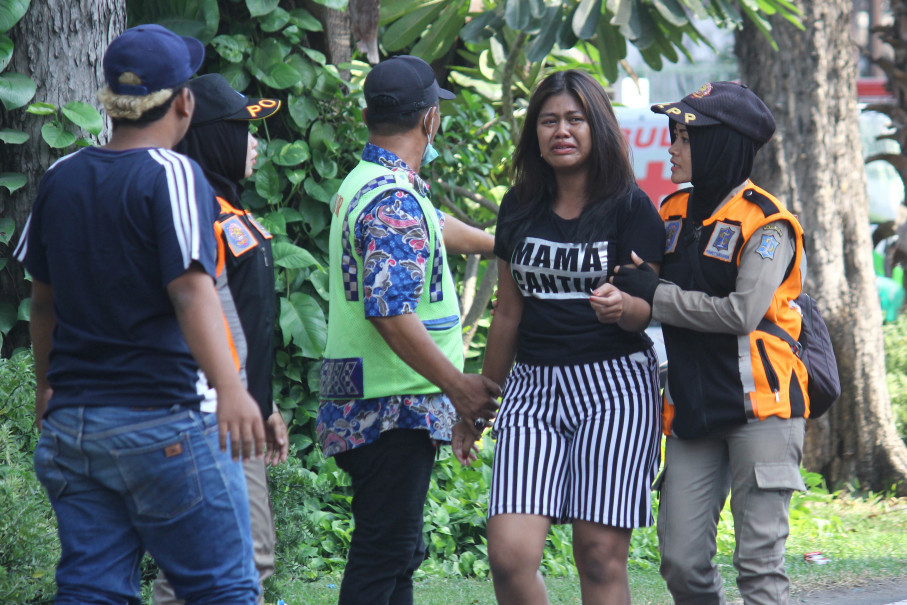Police assist a woman looking for family members near the site of a blast at the Pentecost Church Central Surabaya. (Antara Photo/Moch Asim)