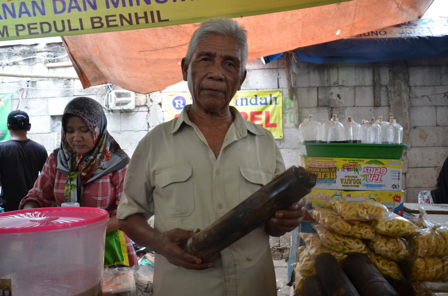 Mr. Mawi stands proudly with his homemade lemang – sticky rice cake cooked in bamboo – at Benhil Market. (JG Photo/Cahya Nugraha)