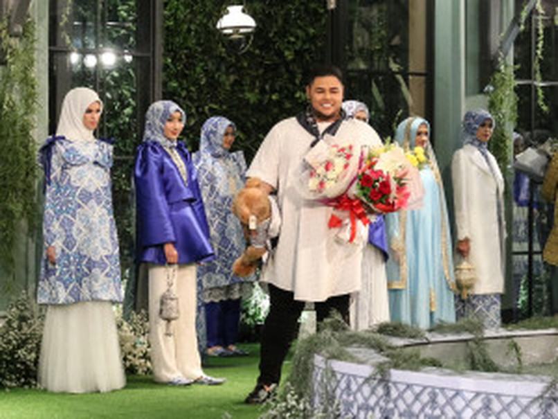Ivan Gunawan receives flowers after the fashion show. (Photo courtesy of Tim Muara Bagdja)