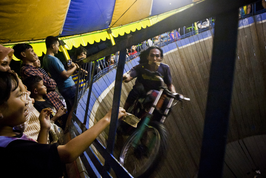 A rider reaches for a tip from a spectator. (JG Photo/Yudha Baskoro)