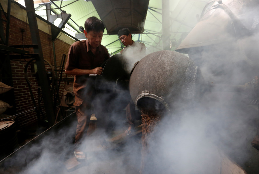 Widya Pratama, the owner of Kopi Aroma, roasts locally grown coffee beans with a traditional wood heated roaster in Bandung, West Java. (Reuters Photo/Willy Kurniawan)
