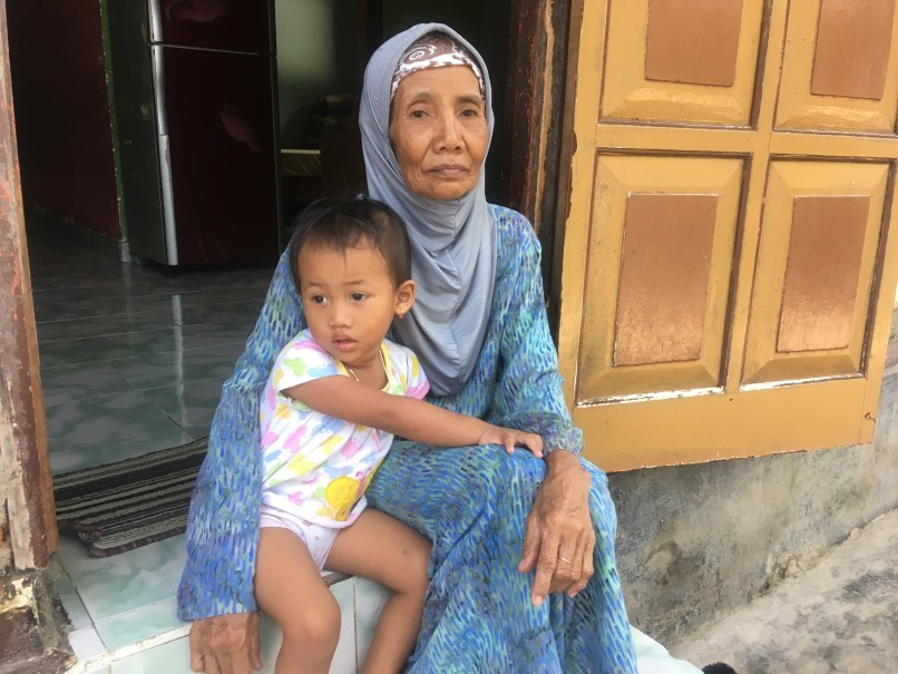 Surayah sits outside her home with her granddaughter in Singaraja, northern Bali, on June 8. (Reuters Photo/Michael Taylor)