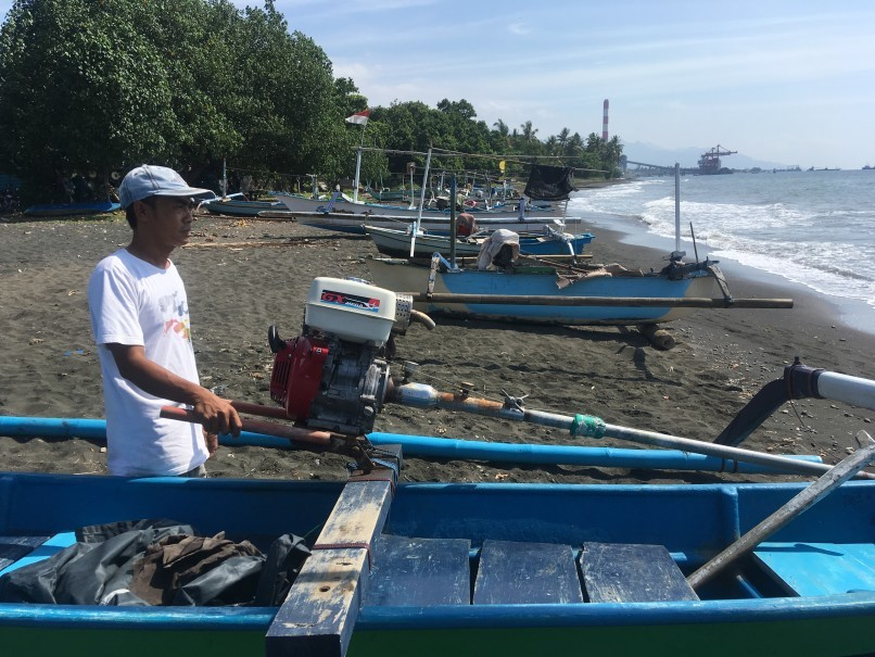 Fisherman I Putu Gede Astawa stands by his boat on Muding Beach in northern Bali, with the coal-fired power plant in the background. (Reuters Photo/Michael Taylor)
