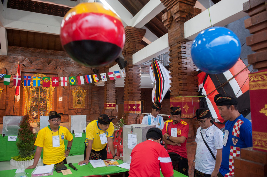 Election officials prepare for the start of voting at a polling station with a World Cup theme in Badung, Bali, on Wednesday (27/06). (Antara Photo/Nyoman Budhiana)