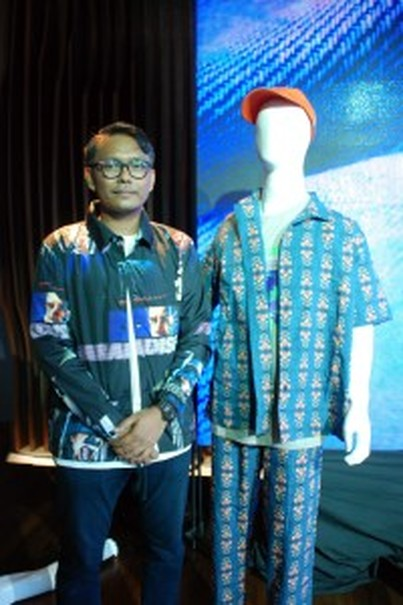 Hendrick Setio poses next to an outfit by Paradise Youth Club. (Photo courtesy of Bekraf)