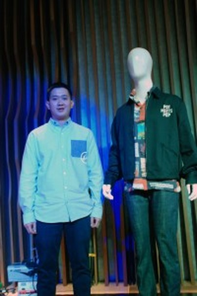 Barry Arief Wijaya poses next to an outfit by Pot Meets Pop. (Photo courtesy of Bekraf)