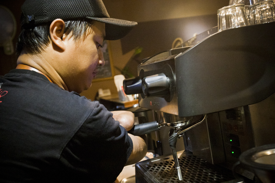 Eko operates an espresso machine. He is still learning to make coffee latte, because some parts of the process, such as steaming the milk and creating latte art, are very difficult for a person with no fingers. (JG Photo/Yudha Baskoro)