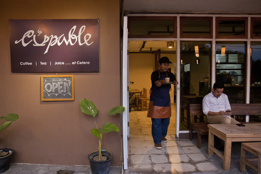 Eko serves a customer at Cupable Café. His dream is to open his own café one day where he can employ people like himself, living with disabilities. (JG Photo/Yudha Baskoro)