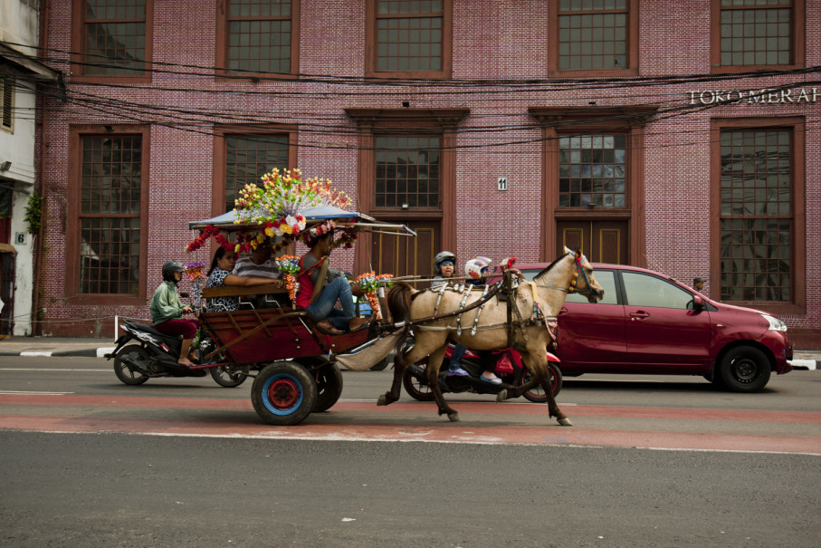 A horse-drawn carriage with tourists passes by Toko Merah, one of the old town's hallmark buildings. (JG Photo/Yudha Baskoro)