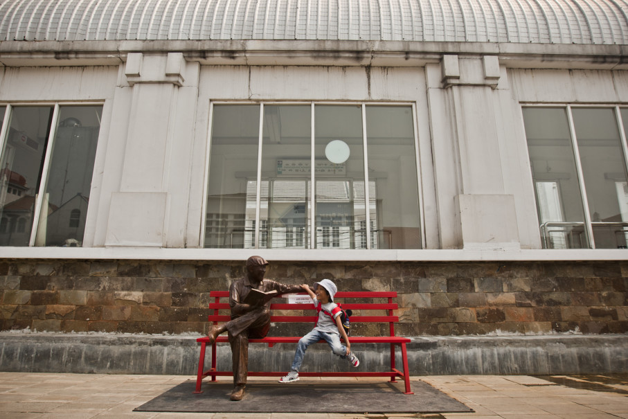A child sits next to a sculpture of a reading man. (JG Photo/Yudha Baskoro)