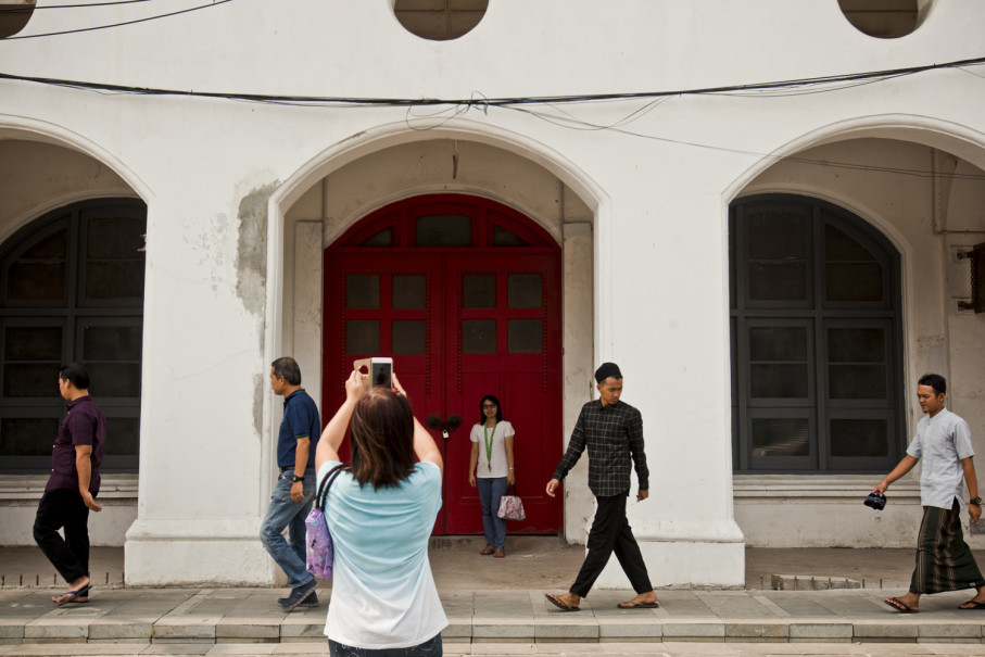 People take pictures in front of a heritage building. (JG Photo/Yudha Baskoro)