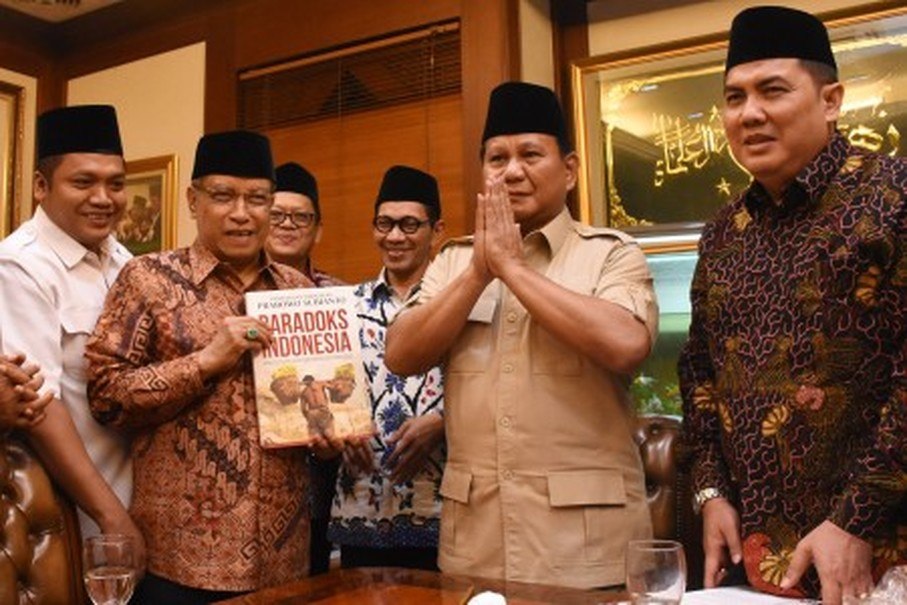 Said Aqil Siroj, second left, receives a book from Prabowo Subianto, second right, on Monday (17/07). (Antara Photo/Junaidi Mahbub)