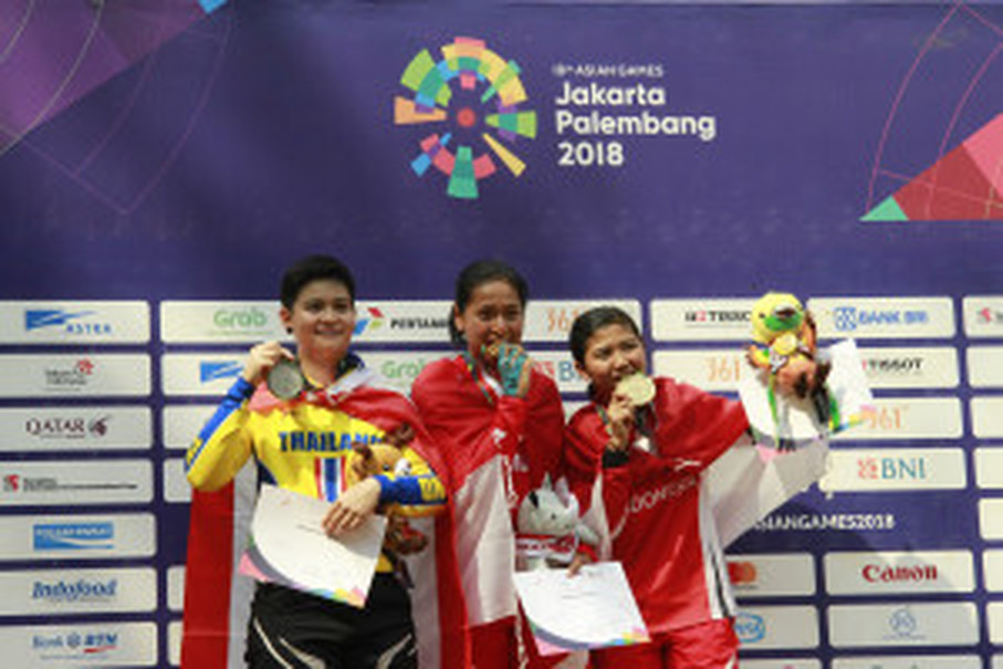 Tiara Andini Prastika, center, Vipavee Deekaballes, left, and Nining Porwaningsih show off the medals they won in the women's downhill cycling event. (Antara Photo/Inasgoc/Dwi Andri Purwanto)