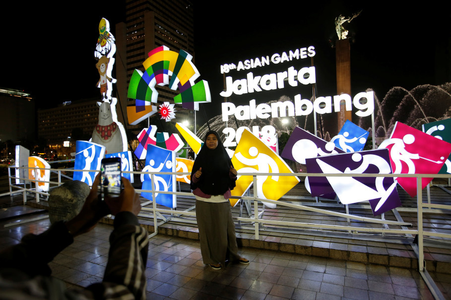 A woman poses for a photo next to a sign promoting the Asian Games in Central Jakarta on Wednesday. (Reuters Photo/Willy Kurniawan)